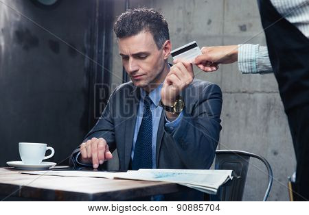 Confident man paying with credit card at the restaurant