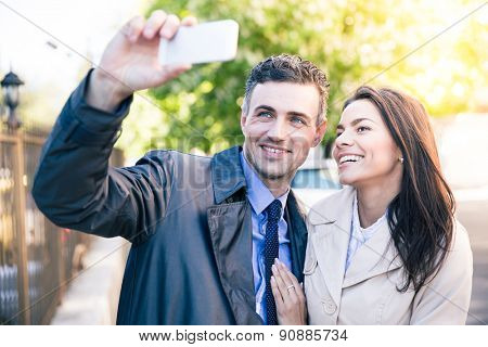 Laughing woman and happy man making selfie photo on smartphone outdoors