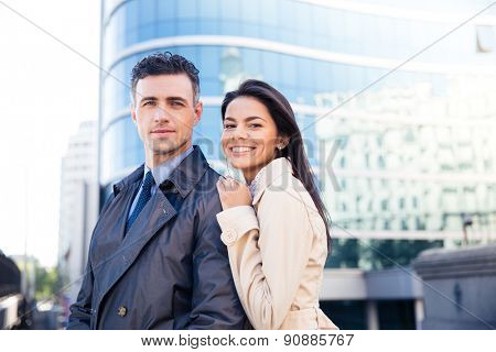 Portrait of a young smiling couple standing in front of a business center. Looking at camera