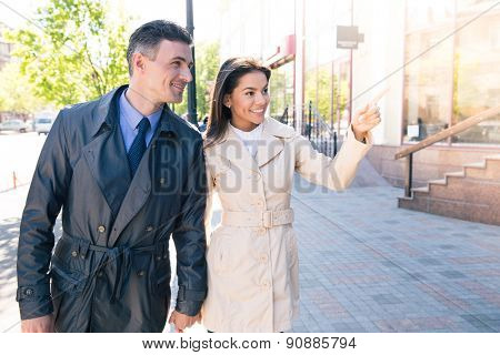 Happy woman pointing on something to her husband outdoors