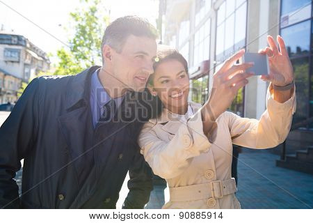 Cheerful young couple making selfie photo on smartphone outdoors in the city