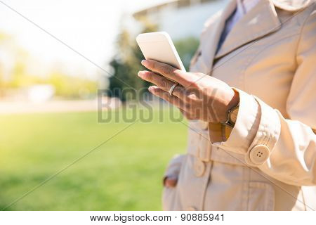 Closeup image of a female hand holding smartphone