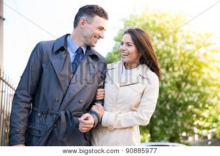 Happy young couple walking and talking outdoors