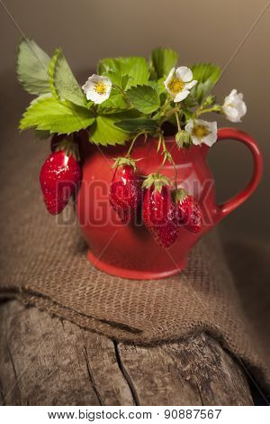 ripe juicy berries and jug on piece of wood