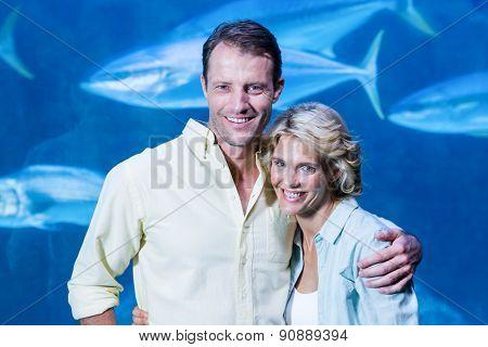 Happy couple looking at camera beside the fish tank at the aquarium