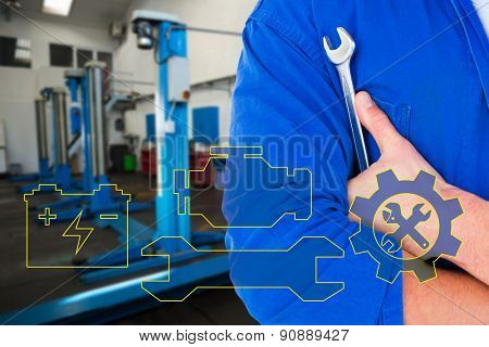 Male mechanic holding spanner on white background against empty work stations