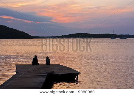 Couple On Pier With Sunset