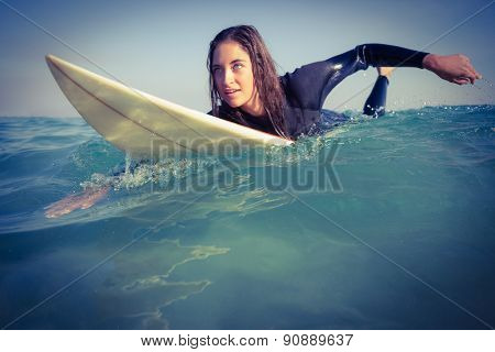 woman in wetsuit surfing on sunny day