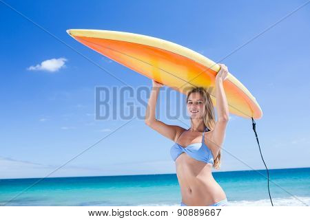Pretty blonde woman holding surf board at the beach