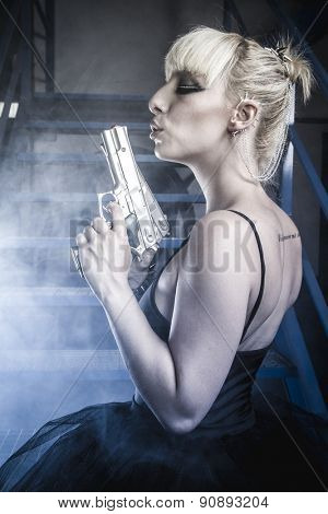 Sensual Blonde with pistols and dressed in costume ballet dancer