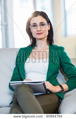 Psychologist sitting on the couch and looking at camera in the office