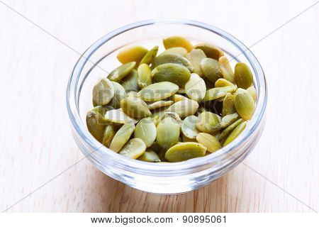 Pumpkin seeds in the glass bowl isolated