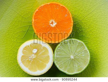 Mandarin, lemon, and green lime slices isolated on green background