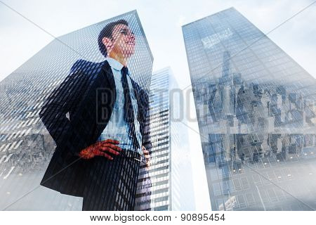 Cheerful businessman with hands on hips against low angle view of skyscrapers