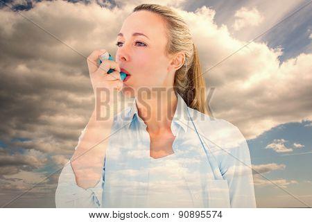 Pretty blonde using an asthma inhaler against sky