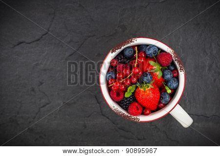 Fresh summer berries in vintage mug over black background,top view