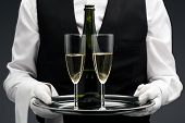 stock photo of flute  - butler with two champagne flute and bottle on tray - JPG
