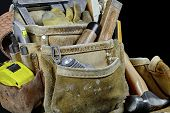 stock photo of leather tool  - Rugged worn carpenters leather work bags and belt with construction tools and hammer isolated on black and selective focus on leather texture - JPG