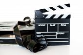 stock photo of mm  - Movie clapper and vintage 35 mm film cinema reel on white background filmstrip unrolled selective focus - JPG