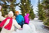stock photo of snowball-fight  - Group of happy kids throw snowballs during game together standing behind the snow wall with fir forest on the background during winter day - JPG