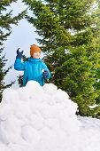 stock photo of snowball-fight  - Boy in blue winter jacket throwing snowballs behind the snow wall with forest on the background - JPG