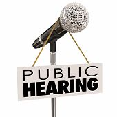 stock photo of hearing  - Public Hearing words on sign around a microphone to illustrate feedback - JPG
