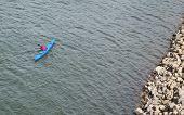 image of shoreline  - Paddler in kayak along the shoreline of Mississippi River - JPG