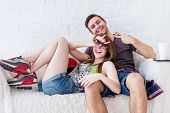 picture of fools  - Friends girl with cup of coffee and guy sitting on sofa at home talking - JPG