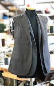 picture of tailoring  - Partially completed hand tailored jackets hanging on a mannequin in a clothing design studio seamstress or tailors workshop - JPG