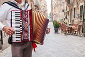 foto of accordion  - Accordion musician playing along the alleys of Ortigia the old part of Syracuse - JPG