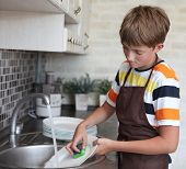 picture of homemaker  - boy doing the dishes in the kitchen - JPG