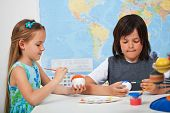 stock photo of face painting  - Kids painting the planets in art and science class  - JPG