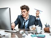 stock photo of loafers  - Office worker with paper plane in his hand typing on a computer keyboard - JPG