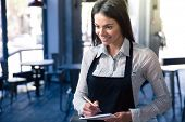 picture of apron  - Smiling beautiful female waiter in apron with notepad and pen in cafe - JPG