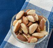 stock photo of brazil nut  - Organic Brazil nuts in a glass bowl on blue napkin - JPG
