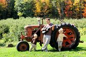 stock photo of tractor  - A Father and his two young boy children are relaxing on a farm playing guitar by an old tractor in the autumn woods - JPG