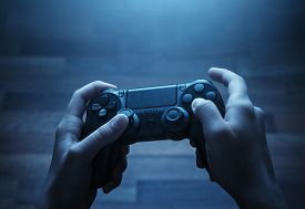 picture of analogy  - Close up of child hands playing the video game late at night - JPG