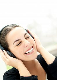 stock photo of vivacious  - Vivacious young woman enjoying her music laughing as she holds her headphones to her ears close up of her face with her eyes closed in bliss - JPG