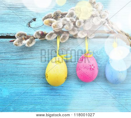 Happy Easter. Pussy-willow and colorful eggs on wooden background.