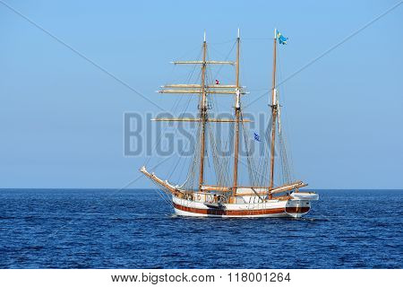 Old Historical Tall Ship With White Sails In Blue Sea