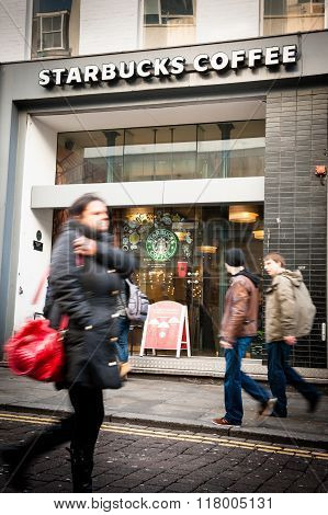 People Walk Past a Branch of Starbucks Coffee shop in Liverpool