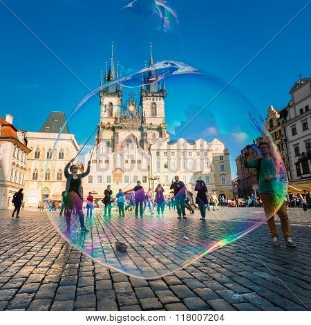 Unidentified young woman makes soap bubbles in Old Town Square in Prague, Czech Republic