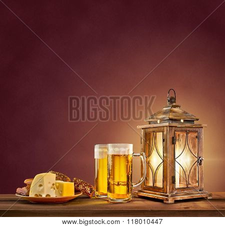 old lantern with beer, cheese and bread on vintage background
