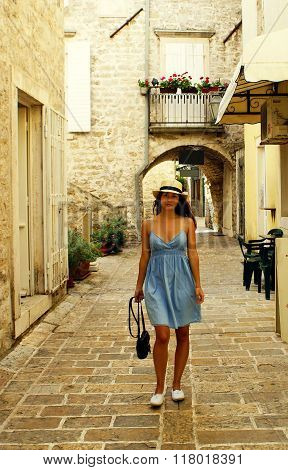 Beautiful Girl In A Sundress And Hat Walks Through The Narrow Streets