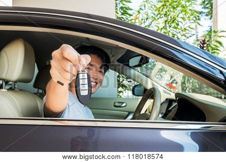 Asian guy with smiling face show his new car's key remote