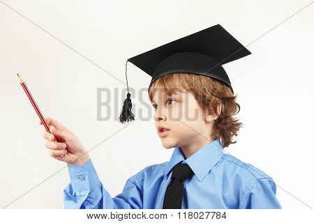 Little serious boy in academic hat with pencil on white background
