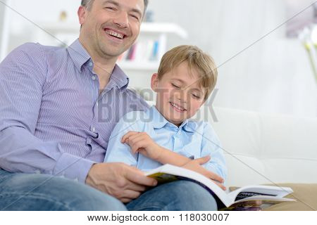 Father and son laughing while reading book