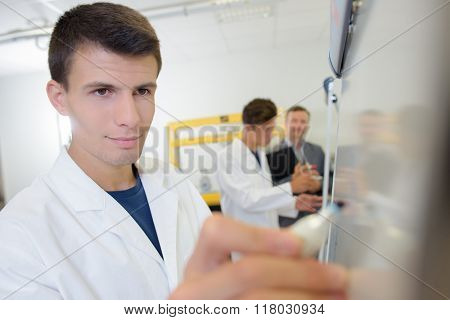 Young man writing on easel