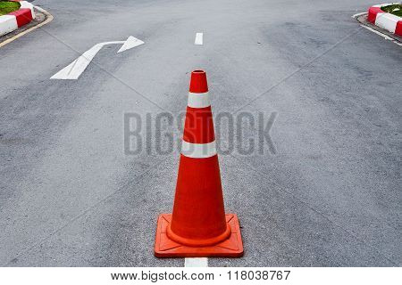 Orange traffic cone on asphalt road with white arrow to turn right ahead.