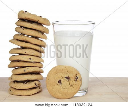 One Dozen Chocolate Chip Cookies Stacked Precariously Next To Glass Of Milk